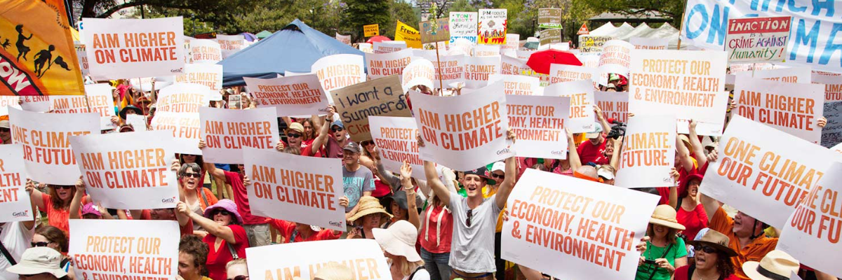 """GetUp members protesting with signs saying """"aim higher on climate"""""""